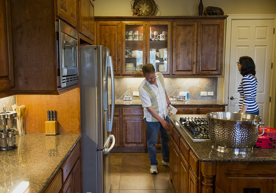 Prospective home buyers view a kitchen while touring a house for sale.