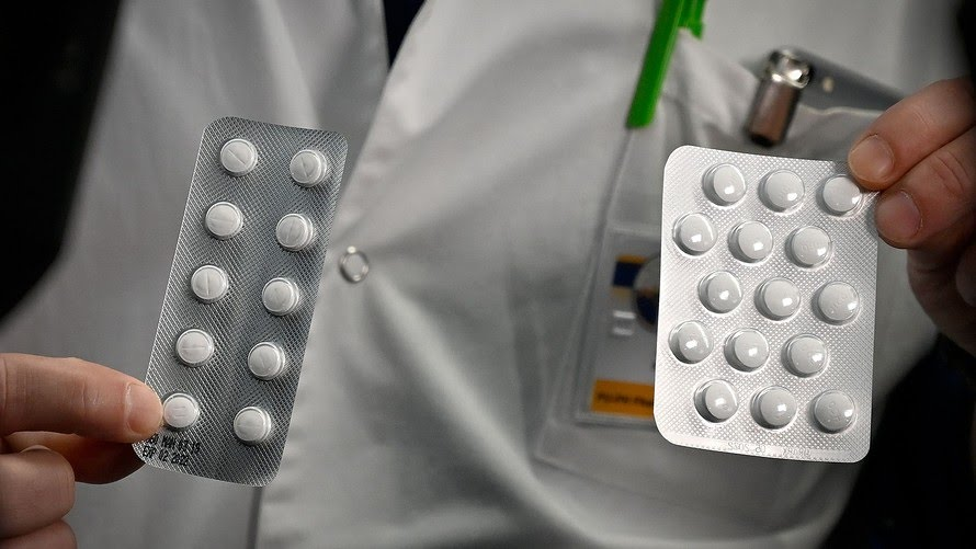 Medical staff shows packets of a Nivaquine, tablets containing chloroquine and Plaqueril, drugs that has shown signs of effectiveness against coronavirus.